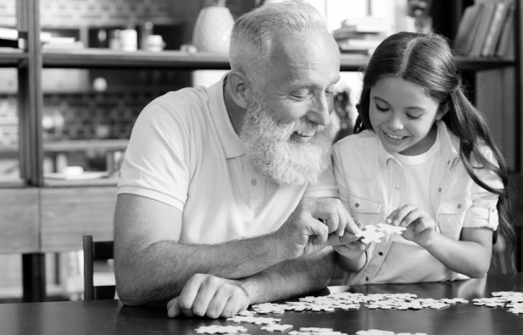 Grandfather and girl chatting while playing jigsaw puzzle