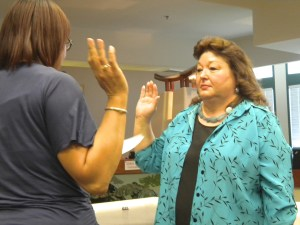 Cindi Delaney is sworn in by city clerk Cherry Lawson as city councilor. Photo by Burton Weast.