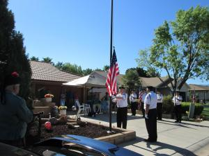 Attendees look on as Tony Hardway raises the flag on the new pole dedicated to Bill Strickland. Photo by Stephanie Frehner.