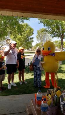 Blake Syndergaard and Nancy Hewett with the Mesquite Chamber, left, congratulate the race winner, Loretta Green, right as she stands with Derby the Duck. Green's husband was the big winner of the day as three of his six ducks won prizes. Photo by Stephanie Frehner.