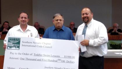 From left to right, Stephen DiGiovanni and David Goldstein present Nick Montoya with a check for $1,500 for free toddler swimming lessons. Photo by Stephanie Frehner.