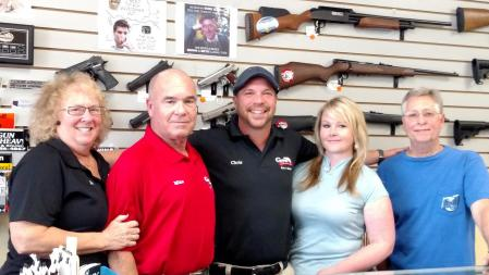 "Guns and Guitars is in the transitional period of moving into the next generation of business. From left to right are current owners Jan and Mike Sullivan, future owners Chris Sullivan with his girlfriend Jenny Perry, and the store's Jack of All Trades, ""Jersey Mike"" Wilbur. Photo by Stephanie Frehner."