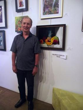 "Ralph Taeger poses next to his oil painting ""Sweet Fruit."" Taeger is a member of the Southern Utah Art Guild, one of the eight art guilds represented at the Mesquite Fine Arts Invitational held in September at the Mesquite Fine Arts Gallery.  Photo by Teri Nehrenz."