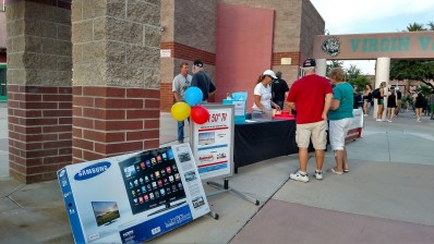 """At the entrance to the Tailgate Party last Friday night was the Kids for Sports table, with the large 50"""" T.V. well-guarded by Mesquite Councilmen Kraig Hafen and Rich Green while Kids for Sports Foundation Advisory Board Member Nancy Hewett takes care of ticket buyers. Photo by Stephanie Frehner."""