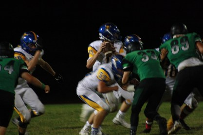 Bulldog lineman (from left to right) Arden Bundy #64, Jayden Perkins #33 and Chase Henderson #89 put defensive pressure on Pirate quarterback Nate Cox during the Dawgs 34-0 loss Friday night in the Dawg Pound. Photo by Lou Martin
