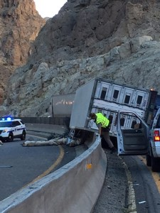 A semi-truck carrying a load of pigs experienced a mechanical failure Monday afternoon while travelling southbound on I-15 through the Virgin River Gorge, overturning and gathering 400 feet of glare screen with it. Submitted Photo.