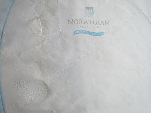 Message in a bottle from Norwegian Cruise Lines, close up.