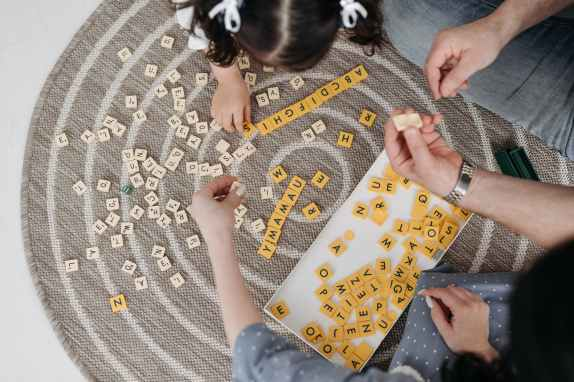 high angle shot of family playing scrabble