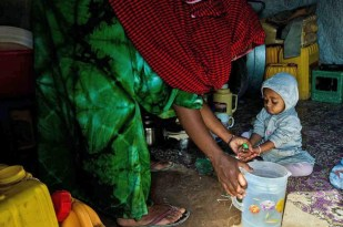 Obah's mother Ruman washes her daughter's hands before giving her a specialized nutrient-dense supplementary food. (Credit: WFP/Kabir Dhanji)