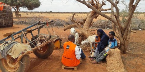 A Norwegian Refugee Council worker in southern Somalia helping a widow and mother of five Faduma Ali Abdulahi to take part in a cash assistance program to buy water and food, which have become more expensive due to the drought. (Credit: Dahir Mumin/NRC)