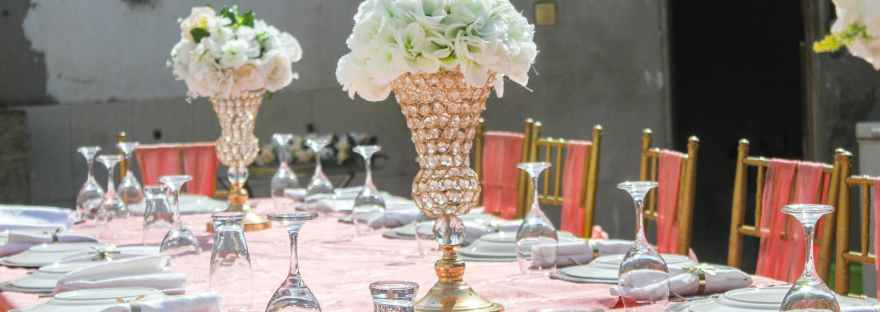 banquet table with dishware and flowers on wedding day