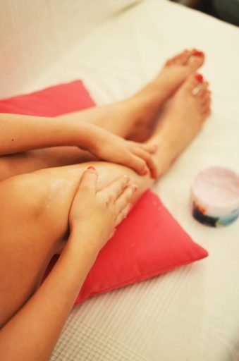 Woman putting lotion on legs