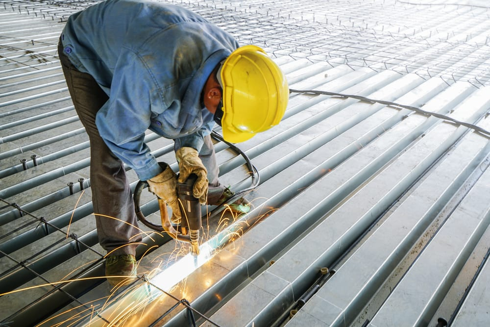 Man welds metal deck slab of mezzanine floor in construction industrial building