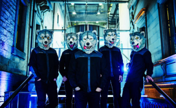 Man with a mission band photograph. The band members are casually standing in an alley while all wearing giant wolf heads which they wear on stage while performing. I swear I'm not making this up.