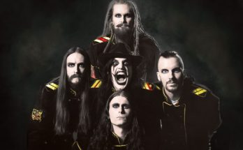 Avatar Band photo. The band are in front of a dark grey background with only their heads and shoulders visible. The five of them are arranged so that their heads are in a cross shape.