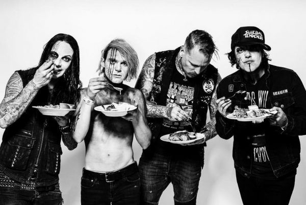 Combichrist black and white band photo. The band are dressed in denim and wearing different facepaints, each of them eating a plate of food.