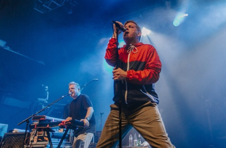 Photo of the singer and keyboardist from the band A playing live. The background of the photo is lit with blue and white lights. The singer is in the foreground in stark contrast due to his red and navy anorak jacket and light brown trousers. The keyboardist is also singing while playing.