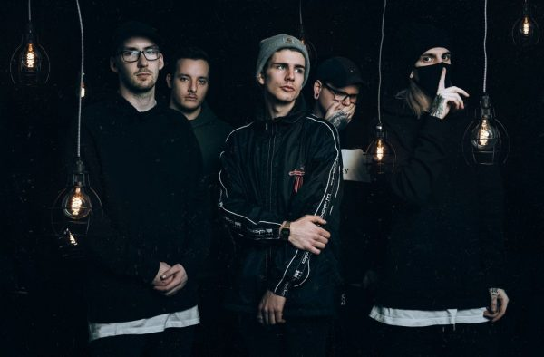Alpha Wolf band photo. The band are pictured in a black room with lightbulbs hanging in front of them. The five members of the band are wearing streetwear - beanies, hoodies, baseball caps and glasses.