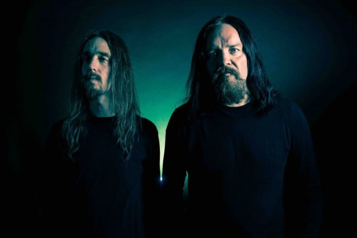 A photo of the band Cadaver, both members are dressed in black. The photography is dimly lit with a dark green background. Anders Odden stands on the right, he has long black hair and a thick goatee with piercing eyes. Dirk Verbeuren is on the left, he looks towards our left, he is thin with long brown hair and a thin goatee.
