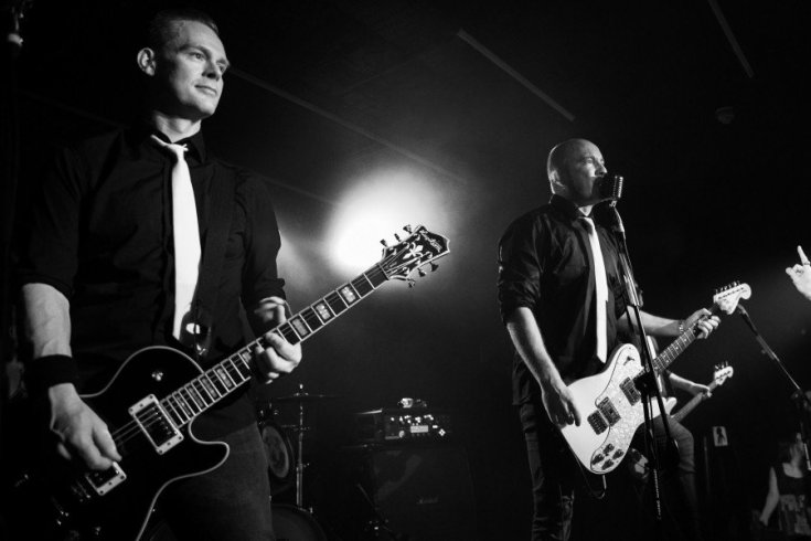 Black and white photo of Eureka Machines' Chris Catalyst and uh the guitarist, Dave. Both are dressed in black jeans, black shirts with white ties.