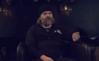 JB of Grand Magus sitting in a leather chair, wearing a hoodie and beanie.