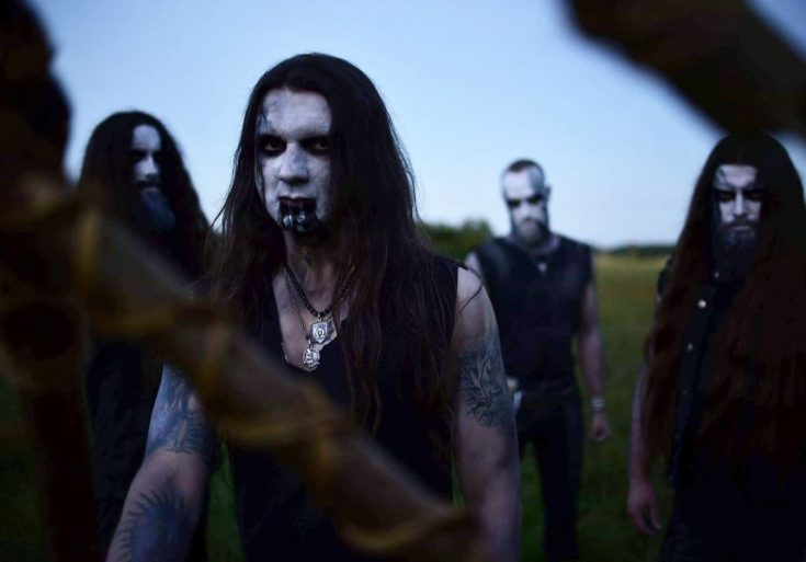 Colour photograph of the band hate. They are stood in a field with a pale blue sky behind them. The band wear black sleeveless shirts, white facepaint and black paint around their eyes and mouths. Something obscures parts of the image, it appears to be a handmade weapon in the foreground, almost hitting the camera.