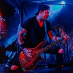 The Raven Age's bassist Matt Cox plays with a red light shining on him and reflecting off his bass guitar.