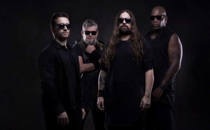 Sepultura colour photo of the band. They are all dressed in black and wearing sunglasses in front of a black backdrop.