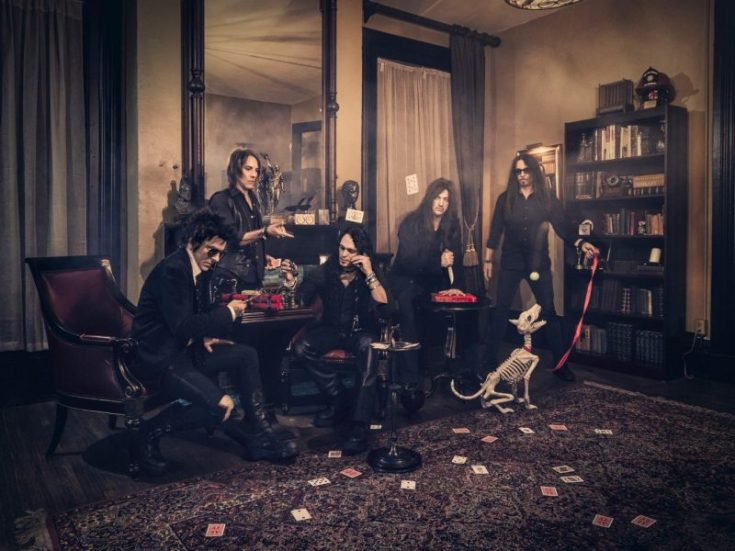 Photo of Skid Row. The band are in an old style room with a bookcase, tables and chairs. Two of the band members sit at a table making sticks of dynamite. Another member is throwing playing cards. A fourth member is sitting at a second table playing Five Finger Fillet (a game where you stab in between your fingers in a particular order with a knife). The last member of Skid Row stands with the skeleton of a dog on a leash.