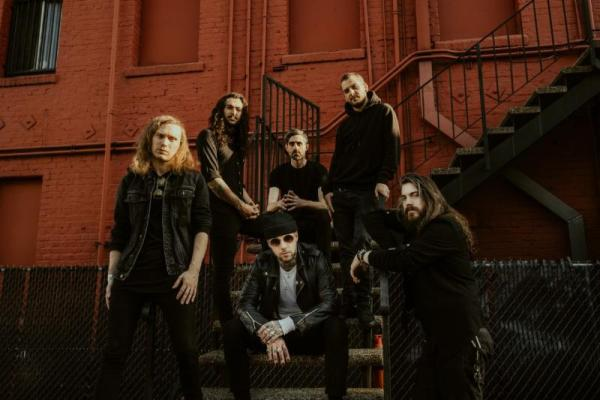 Betraying the Martyrs band photo. The band are all dressed in black and are posed around a fire escape outside a red bricked building.