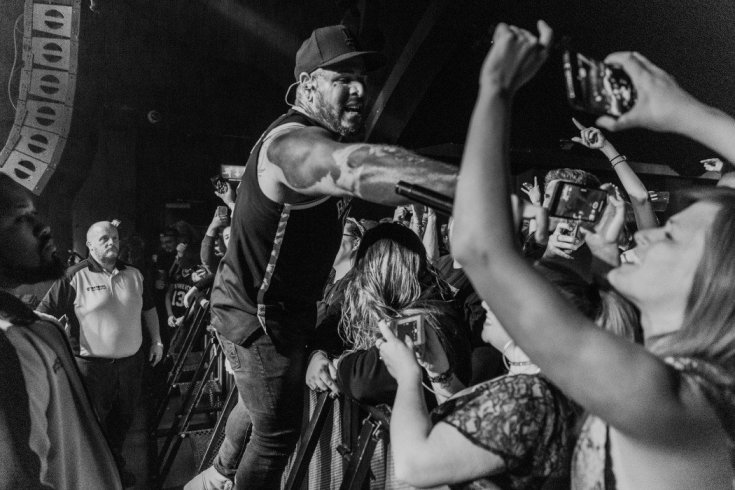 Tommy Vext of Bad Wolves stands on the barrier holding the microphone for a fan to sin into, black and white photo.
