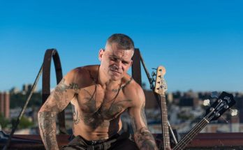 Colour photo of Harley Flanagan of Cro-Mags. He is sitting on a roof with a city behind him. The necks and head of two bass guitars are visible, propped up next to him. He is topless and sitting slightly hunched forwards, covered in tattoos. He has short cropped hair and his face is somewhat scrunched up as if the sun is too bright. He looks intense and weathered.