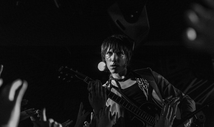 Black and white image of Palaye Royale guitarist Sebastian Danzig playing while looking intensely into the camera while the hands of fans reach up towards him