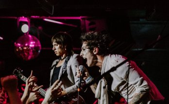 Palaye Royale live colour photo. Remington Leith leans over the crowd while singing. In the background Sebastian Danzig plays guitar.