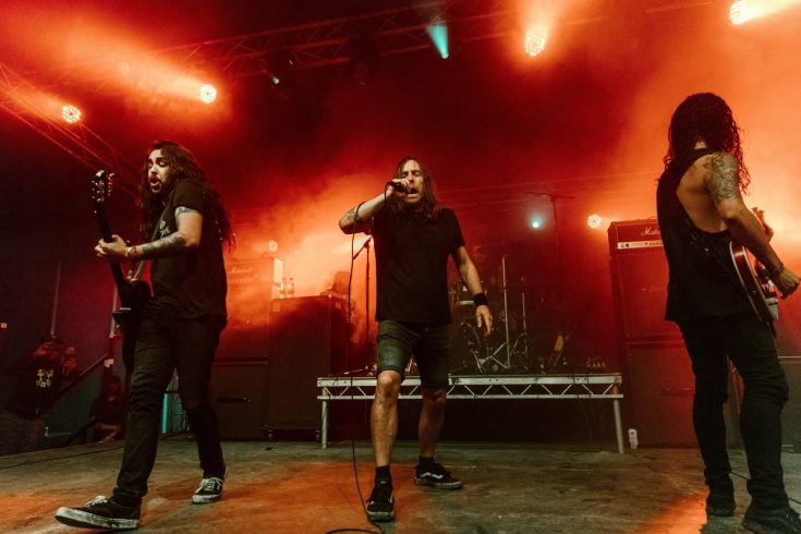 Australian band The Lazys play Bloodstock 2019 in front of a stream of red lights.