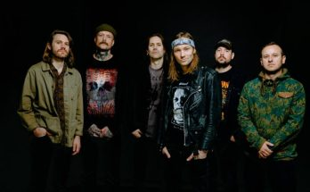 Kvelertak band photo. The band stand in front of a black background with the hands tucked into their pockets