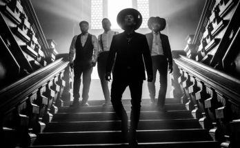 Me and That Man band photo 2020. Black and white photo of the band backlit while walking down a staircase
