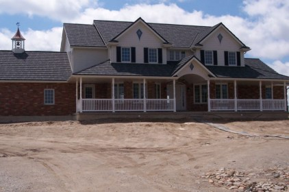 This lovely, custom farmhouse style home features a gorgeous covered porch, a peaked weathervane and bell tower, and a steel shake roof by Metal Roof Outlet, Ontario.