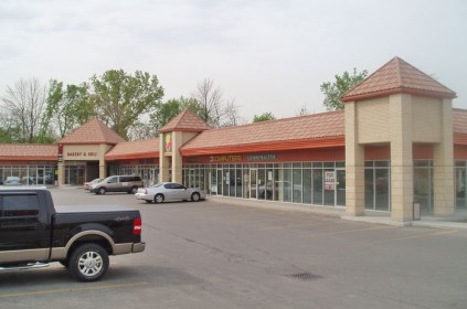 This shopping plaza in Ontario features a clay-coloured steel tile to go with the orange trim.