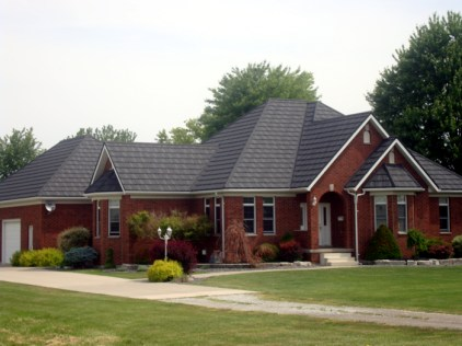 The neutral grey of this steel shake roof by Metal Roof Outlet pairs well with the deep auburn brick of this Ontario home.
