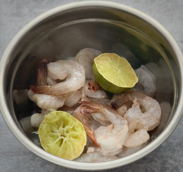 Raw shrimp in a bowl with limes cut in half