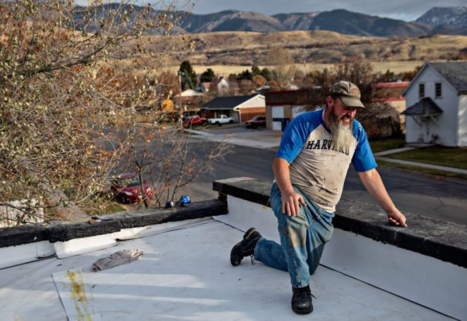 David Gordon, who was arrested at his church after he failed to repay a high-interest loan, works on his roof in Richmond, Utah. (Kim Raff for ProPublica)