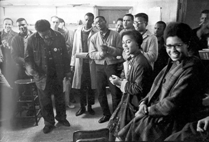 James Forman leads singing in the SNCC office on Raymond Street in Atlanta, (from left) Mike Sayer, MacArthur Cotton, Forman, Marion Barry, Lester McKinney, Mike Thelwell, Lawrence Guyot, Judy Richardson, John Lewis, Jean Wheeler, and Julian Bond, Danny Lyon, Memories of the Southern Civil Rights Movement 123, dektol.wordpress.com