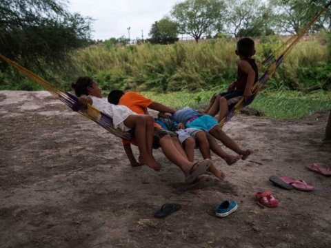 Asylum-seeking children swing in a hammock along the banks of the Rio Grande at a migrant camp in Matamoros, Mexico, on May 15. (Verónica G. Cárdenas for The Texas Tribune/ProPublica)