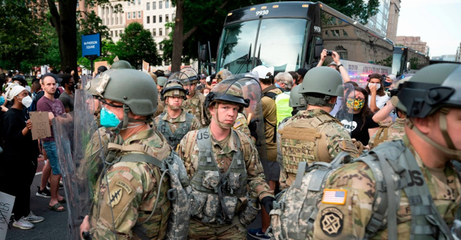Protesters watch as members of the U.S. military walk off a bus near the White House on June 3, 2020, in Washington, D.C.