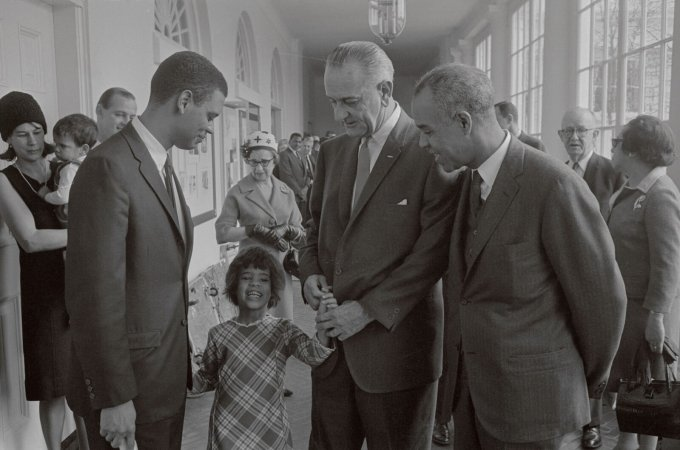 President Lyndon Johnson with Roger Wilkins, left, the second director of the CRS, and Wilkins' daughter at the White House. Johnson created the agency. (Bettmann)