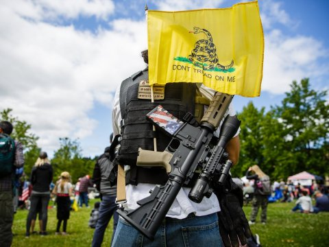 Members of the Patriot militia movement watched the March for our Rights 3 in Olympia, Washington, in June. Jason Redmond / HCN