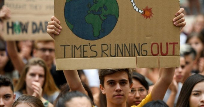 "A demonstrator holds a placard reading ""time is running out"" during a global youth climate action strike in Barcelona, on September 27, 2019 at the end of a global climate change week. (Photo: Josep Lago/AFP)"