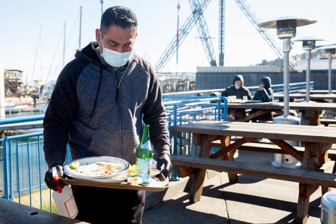 Victor Garcia works to disinfect tables and clear finished plates at Fish restaurant in Sausalito, California, on Jan. 25. Fish was one of the first restaurants to re-open for outdoor dining after Governor Gavin Newsom lifted shelter-in-place orders. (JESSICA CHRISTIAN/THE SAN FRANCISCO CHRONICLE VIA GETTY IMAGES)