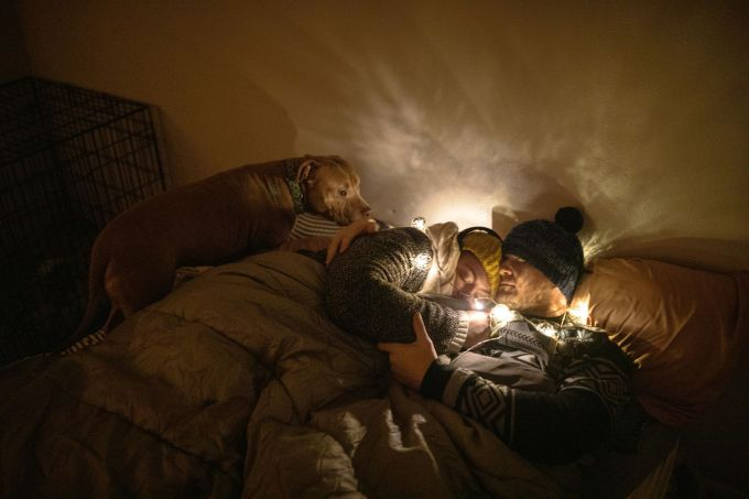 Savannah and Sam Peyton, who were without power for days last week, huddle in multiple layers under a sleeping bag at their home in Austin, Texas, on Thursday night, Feb. 18, 2021. Temperatures plummeted to the teens and single digits across Texas, and at least 58 have died in storm-affected areas across the country from causes including carbon monoxide poisoning, car crashes, drownings, house fires and hypothermia. Credit: Tamir Kalifa/The New York Times/Redux